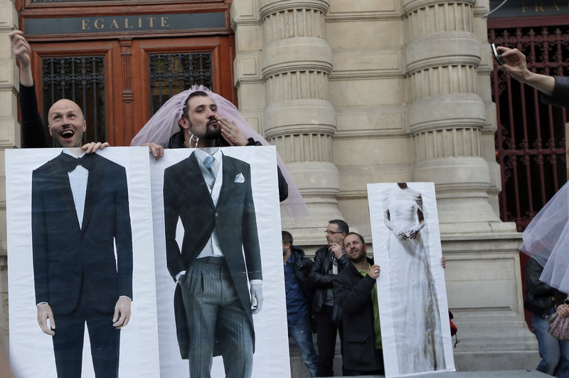 Divisive issue: While pro-gay marriage activists in Paris playfully pose in support of thieir cause, the legalization of same-sex marriage also spurred hundreds of thousands to protest in France's capital. Famous for embracing love and romance, the people of France are not united on this issue.