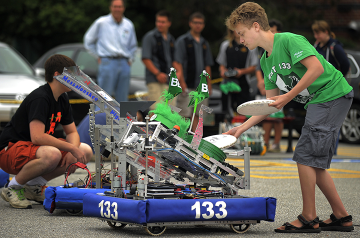 """Aidan Qualey of Bonny Eagle loads flying discs into his team's robot, named """"Sherman,"""" outside Fairchild Semiconductor. Fairchild is contributing $100,000 to start the Robotics Institute of Maine, which hopes to have 1,000 students participating by 2016."""