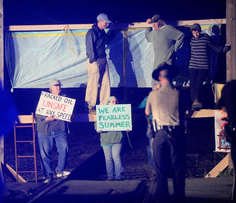 Protesters from a group calling itself 350 Maine erect a barricade on railroad tracks near the Fairfield Town Office on Thursday.