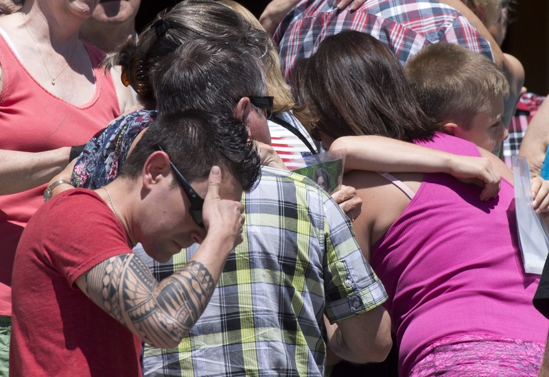 People react as church bells chime 50 times for the victims of the July 6 train crash and blaze in Lac-Megantic, Quebec, Canada, on Saturday. Residents have filed a class-action lawsuit against the railroad.