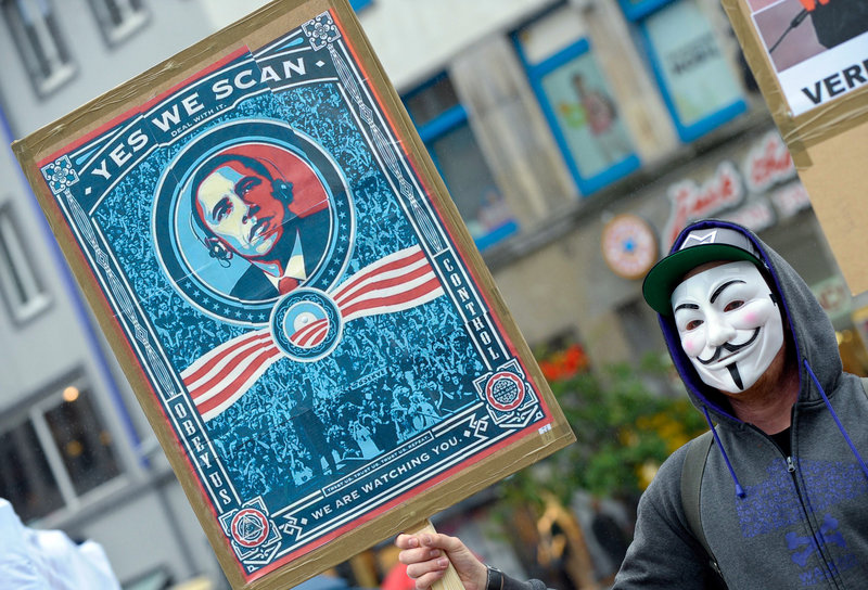 """A demonstrator protests with a poster against the National Security Agency Saturday in Hanover, Germany. Germany's top justice official says reports that U.S. intelligence bugged European Union offices remind her of """"the methods used by enemies during the Cold War."""""""