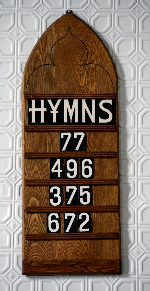 A board lists the hymns for the Sunday service.