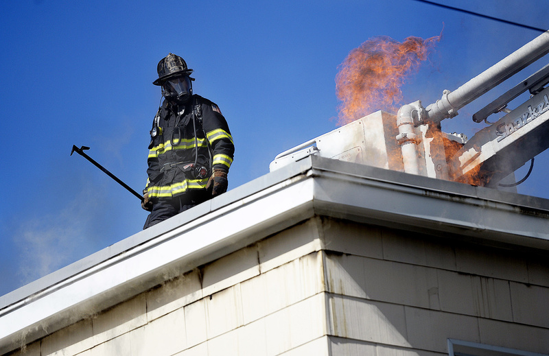 A firefighter pauses while working on the roof to keep an eye on flames at 129 Grant St. in Portland on Wednesday. A two-alarm fire heavily damaged the top story of the three-story apartment building.