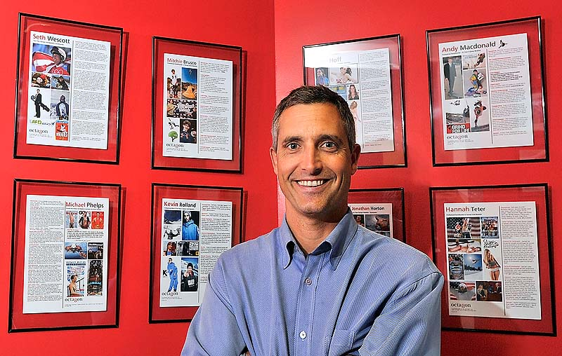 """Peter Carlisle stands in front of a gallery of his clients in his office at the MHG Ice Centre in Saco. He said when he started his own agency in 1997, he considered the growing popularity of action sports, such as snowboarding, and saw opportunity. """"He was a visionary,"""" says his brother, Jeff Carlisle."""