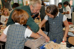 BLAKE HENDRICKSON, artist-in-residence at St. John's Catholic School in Brunswick, helps students build wooden sculptures as part of Arts Are Elementary, which works to connect visiting artists with each grade's curriculum and each school's broader learning goals to illuminate studies and offer unique perspectives.
