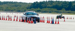 BRUNSWICK OFFICER Dan Sylvain, in rearview mirror, maneuvers through a course of traffic cones Tuesday at Brunswick Executive Airport while instructor Mike Andreotti observes.