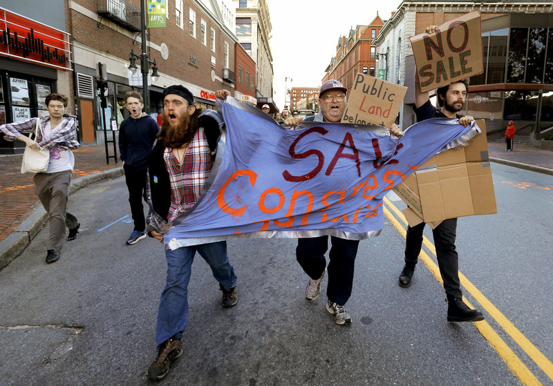 Left to right, Matthew Coffey, Carl McKenney and Michael Anthony lead a march down the center of Congress Street to City Hall on Monday, September 16, 2013, to protest the sale of Congress Square Plaza.