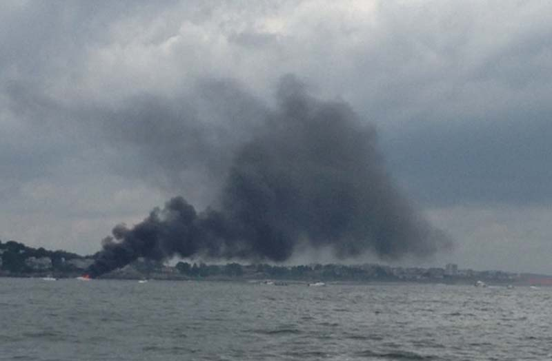 Heavy black smoke billows from a burning boat Sunday afternoon in Portland Harbor. Four people and a dog were rescued by a good Samaritan. No one was hurt.