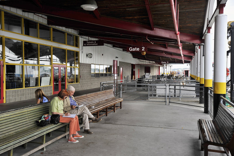 """Travelers sit in the outside waiting area of the Casco Bay Ferry Terminal in Portland on Saturday. A renovation and expansion project will make the terminal """"better, particularly for the customers,"""" Operations Agent Larry Legere said."""