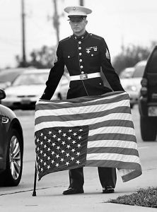 "BEECH GROVE, IND., resident Joseph Lohman, 25, who served as a corporal in the U.S. Marines from 2008-12, shows his concern over the government shutdown by holding an American flag upside down, a signal of distress, just north of I- 465. Lohman is totally disabled from a fall in training and is concerned about veterans not getting their disability checks. "" I'm not protesting,"" said Lohman, ""I'm just standing for what is right."""