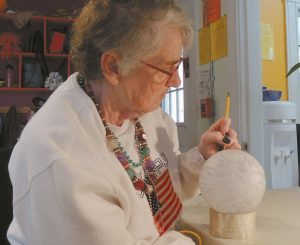 SPINDLEWORKS ARTIST Nancy Bassett sketches fish and ocean creatures on a plastic sphere that eventually will become an ornament to hang on Maine's Christmas tree in the nation's capital. She soon will color or paint the sketches on the finished globe.