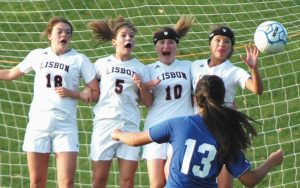 THE LISBON WALL of (from left) Drew Stewart-Staples, Shantal MacWhinnie, Abby Gamache and Jenna Clifford try to block this shot by Oak Hill's Jamie Prue during an MVC girls high school soccer game at Lisbon Falls on Monday. Prue's shot got through, leading to the eventual gamewinning goal as the Raiders came away with a 2-1 win.