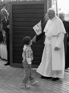 POPE FRANCIS is welcomed by a child as he arrives at the Caritas Reception Center at St. Mary of the Angels, near Assisi, Italy, today.