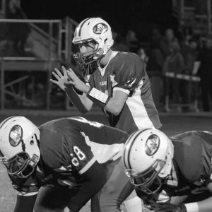 MT. ARARAT HIGH SCHOOL quarterback Dylan Johnson takes the snap behind James Stemp during Friday's Class B matchup in Topsham with Oceanside.