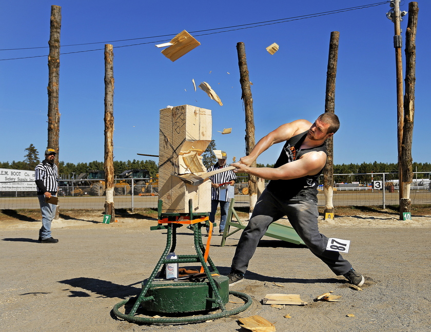 Wood chips fly as Gabe Darling of Shortsville, N.Y., hacks away Monday during the standing block chop at the Fryeburg Fair.