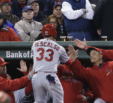 Daniel Descalso of the Cardinals is congratulated at the dugout after scoring on Carlos Beltran's single, the final run of a three-run seventh inning Thursday night that gave St. Louis a 4-2 victory and a 1-1 tie in the World Series. The series will resume Saturday night in St. Louis.