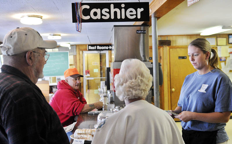 Hi-Hat waitress Caitlyn Laflin, right, gives customers change Monday on the eve of increases in meals, lodging and sales taxes in Maine. Meals and lodging taxes will increase from 7 percent to 8 percent and the sales tax will rise to 5.5 percent from 5 percent.