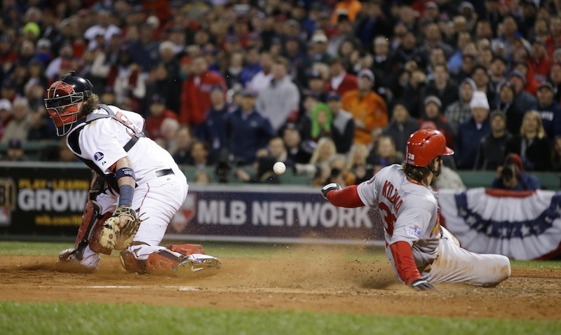 St. Louis Cardinals' Pete Kozma scores on a sacrifice fly as Boston Red Sox catcher Jarrod Saltalamacchia can't handle the throw during the seventh inning of Game 2 of baseball's World Series Thursday, Oct. 24, 2013, in Boston. MLB