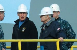 """DEFENSE SECRETARY Chuck Hagel, second from left, talks with officials during Thursday's visit at Bath Iron Works. """"BIW has a very important place in the future of the Navy,"""" he later told shipyard workers."""