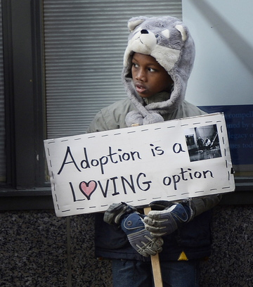 Leslie Sneddon of Richmond, above, protests outside Planned Parenthood on Congress Street in Portland on Friday. Abraham Hebert, 8, of Waterboro, left, holds a sign among the protesters outside the entrance to Planned Parenthood's clinic. Photos by Shawn Patrick Ouellette/Staff Photographer