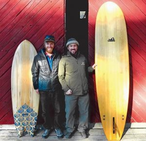 "CHEWONKI SUMMER Wilderness Programs Director Ryan Linehan, right, and Grain staff member Andrew Gardiner show off two handmade surfboards in front of the Chewonki barn as part of the launch of the new Chewonki ""surfboard building expedition."""
