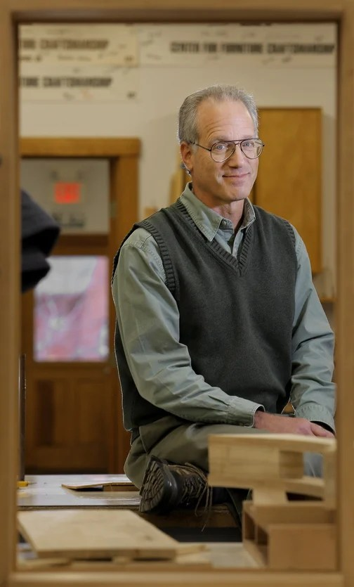 """Peter Korn, director of the Center for Furniture Craftsmanship, poses for a portrait in one of the school's classrooms. He came to Rockport in 1993, where he founded the center that has taught thousands of aspiring craftsmen the art of creating in wood. Korn's new book, below left, is """"Why We Make Things and Why It Matters: The Education of a Craftsman."""" Below, Korn's dancing swan desk."""