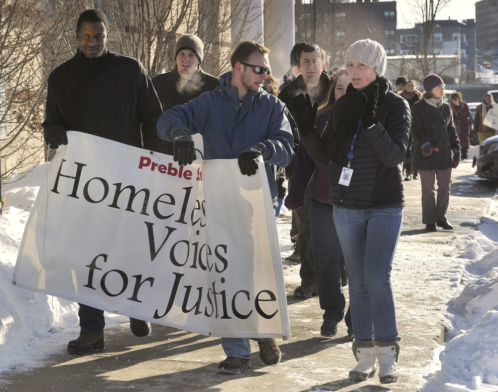 Protesters march in the cold Tuesday at the DHHS office in Portland. A proposed new site for the office would be inaccessible to many who need services, they say.