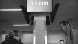 """SEVERAL VIDEO BOARDS along the """"Next Level Experience"""" security checkpoint advise travelers on how long it will take to make it past the TSA inspection at Dallas/Fort Worth International Airport's Terminal E Gate 18."""