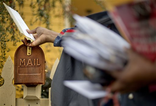 In this February 2013 file photo, U.S. Postal Service letter carrier, Jamesa Euler, delivers mail, in Atlanta. A proposed compromise toward ending Saturday U.S. mail delivery is falling flat with unions while getting the support of a Senate committee chairman.
