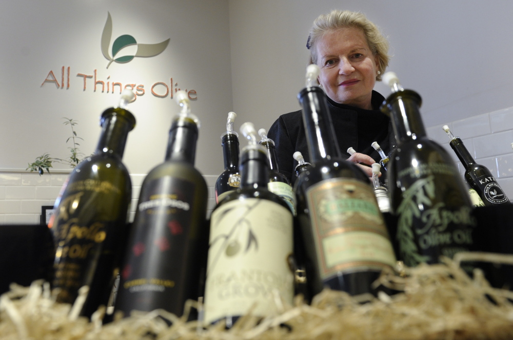"""Patricia Darragh, executive director of the California Olive Oil Council, shows off a collection of California olive oil. In another decade or two, Americans may be more familiar with the domestic variety. """"We're where the California wine industry was 20 or 30 years ago,"""" she says."""
