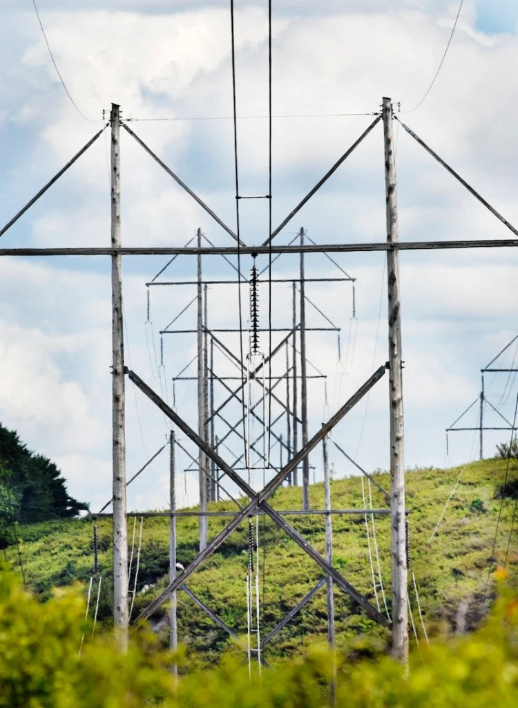 In this 2008 file photo, transmission lines cross Route 201 in Topsham. Two companies have become the first to publicly acknowledge a desire to compete for anticipated multimillion-dollar transmission line projects through Maine.