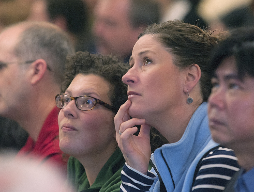 University of Maine employees Erin Straine, left, and Faith Erhardt of the College of Education and Human Development in Orono digest the figures presented on an overhead display during a budget presentation to employees at the Wells Conference Center on Friday.