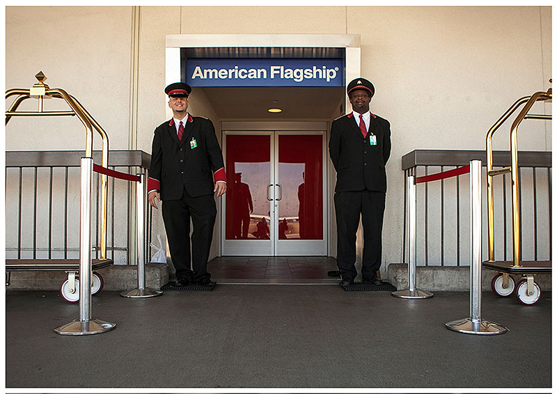 American Airlines skycaps Alex Abel Gonzalez, left, and Frederick Pearson wait outside the AA Flagship lounge at Los Angeles International Airport