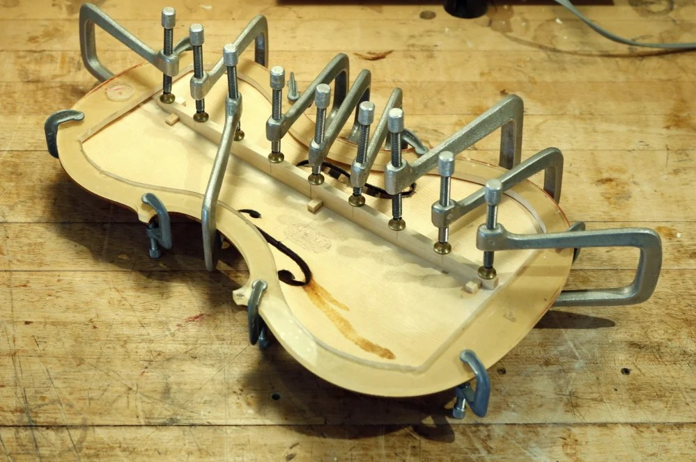Clamps hold a bass bar in place while the glue holding it in place dries on a bench in the Artistic Artisans workshop in Portland Thursday. Jonathan Cooper, owner of Artistic Artisans, made the violin in 2002 and was repairing it for Mark O'Connor after the violin was damaged.