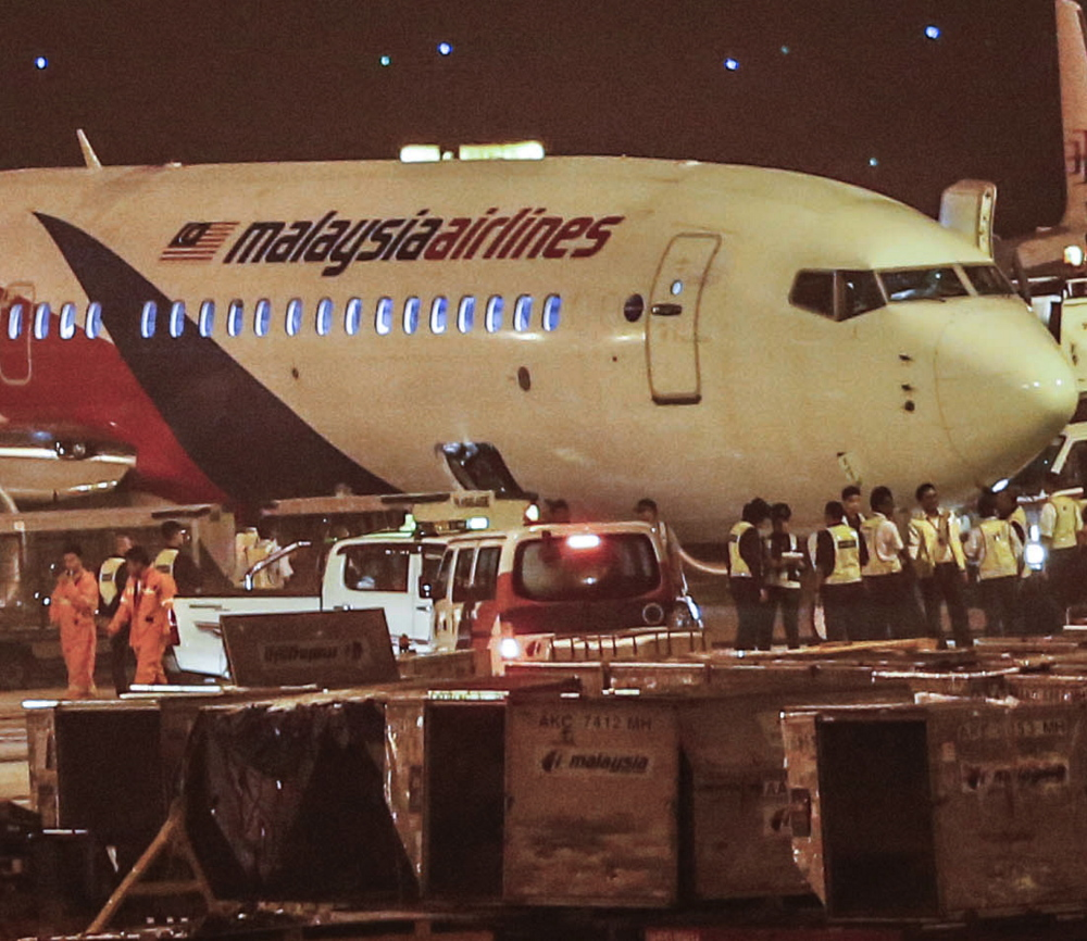 The ground crew checks the Malaysia Airlines Flight 192 bound for Bangalore, India, that turned back to Kuala Lumpur International Airport in Sepang, Malaysia, on Monday.