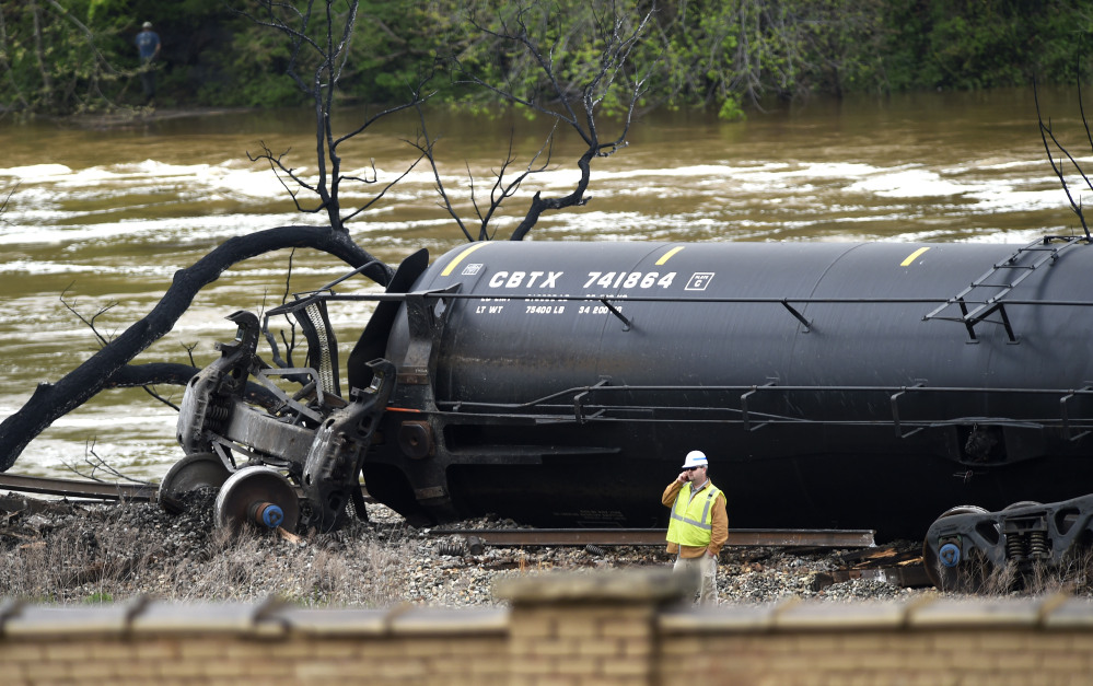 A worker stands Thursday by a damaged tanker car where several CSX cars carrying crude oil derailed and caught fire along the James River near downtown Lynchburg, Va.