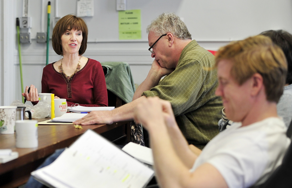"Monica Wood meets with Portland Stage Company actors – including Daniel Noel, center, and Dustin Tucker, foreground – during a reading of her play ""Papermaker."" The work is based on an earlier novel, ""Ernie's Ark,"" which centers on two families who collide during a strike at a paper mill."