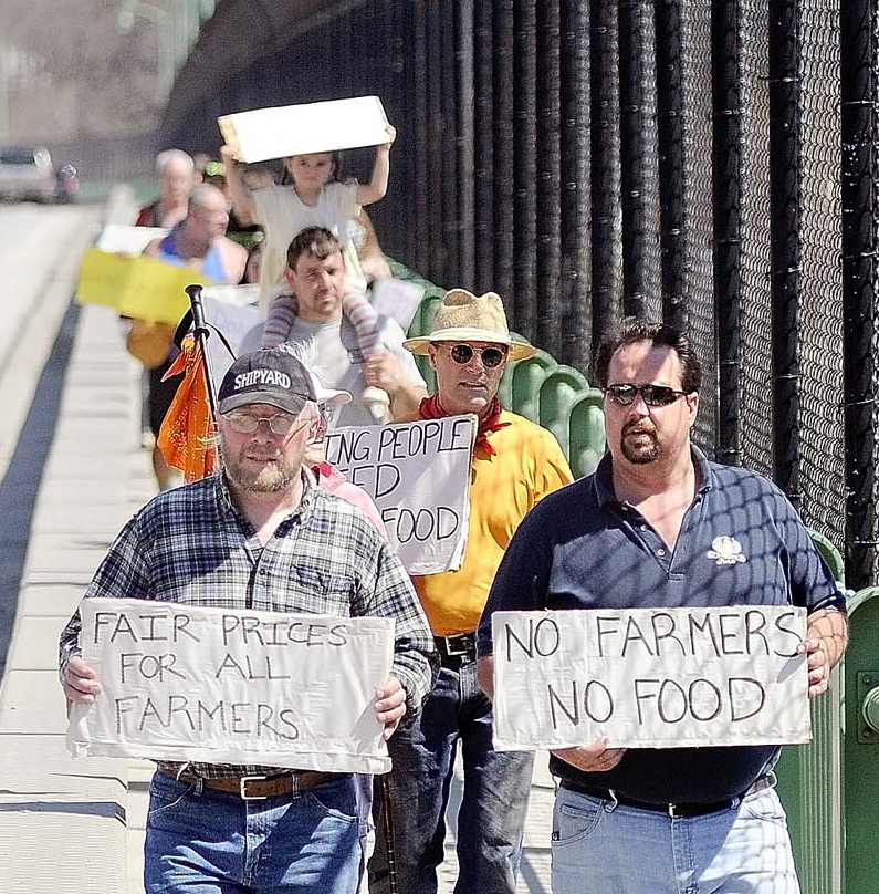 Dan Brown, right, owner of Gravelwood Farm in Blue Hill, leads supporters over a bridge during a 2012 march in Augusta.