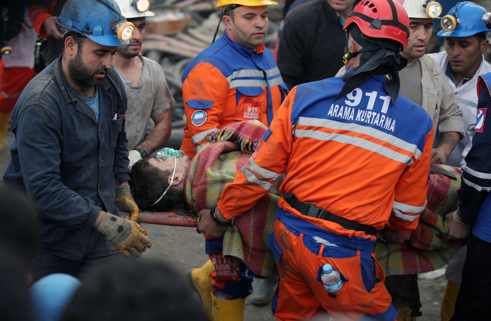 Rescue workers carry a miner rescued from the mine in Soma early Wednesday. Turkey's energy minister said the fire was still burning inside the mine 18 hours after the blast.
