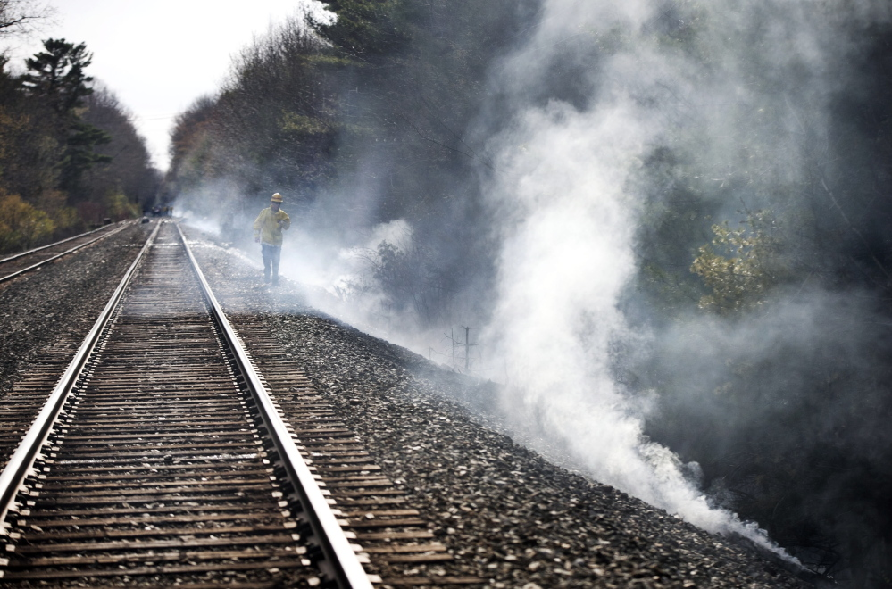 A firefighter walks near railroad tracks where a brush fire started and spread through a campground in Old Orchard Beach on May 8.