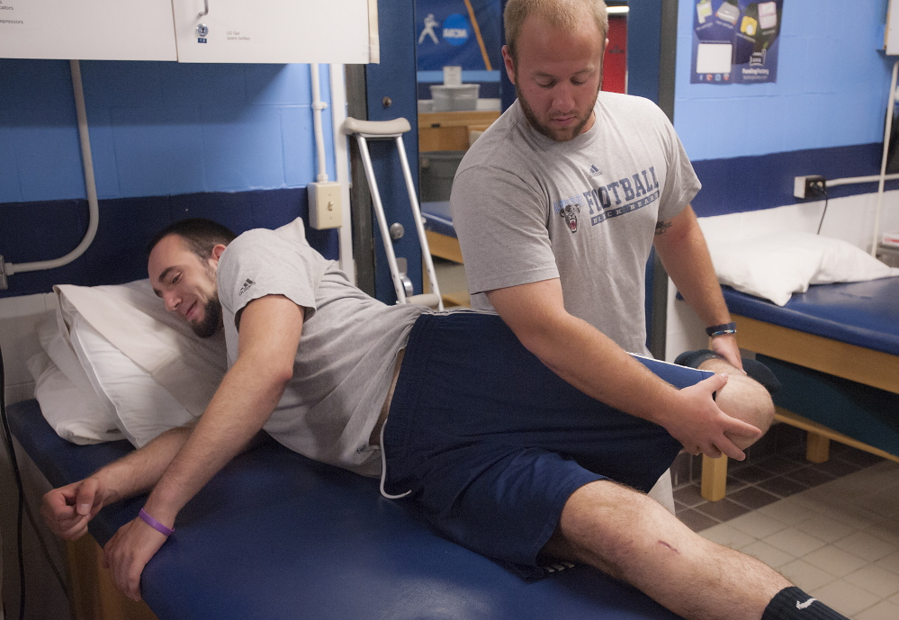 """University of Maine trainer Ben Randall works on the left knee of Kurt Massey, a defensive end who tore his ACL during spring practice. """"It's been kind of bad,"""" Massey said of the loss of summer income and the medical bills his family's insurance carrier faces."""