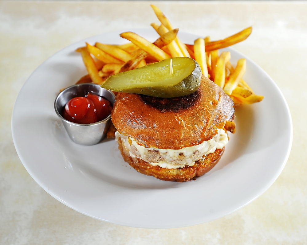 Grass-fed burger with griddled onion and sharp cheddar on a brioche bun, with crunchy fries, a pickle and ketchup.