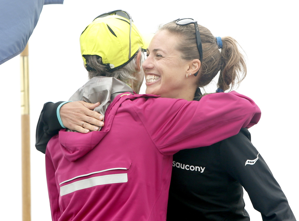 Michelle Lilienthal of Portland receives a hug from Joan Benoit Samuelson after setting a course record for Maine women in 33:38.8 at the TD Beach to Beacon 10K in Cape Elizabeth on Saturday.