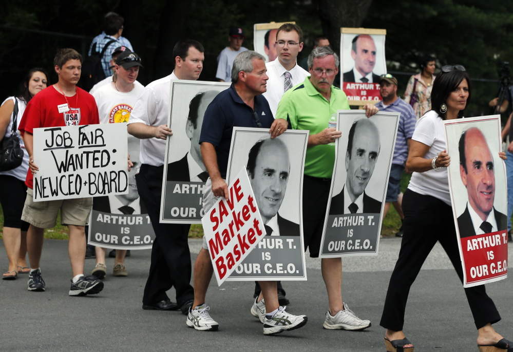 "Protesters holding ""Arthur T"" signs picket outside a Market Basket supermarket job fair in Andover, Mass., on Monday. Market Basket stores in Maine, New Hampshire and Massachusetts have reportedly lost tens of millions of dollars in business since Arthur T. Demoulas was fired in June."