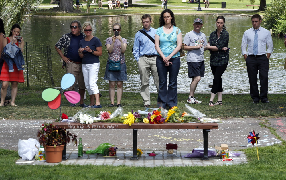 "People pause by a bench Tuesday at Boston's Public Garden, where a small memorial has sprung up at the place where Robin Williams filmed a scene during the movie ""Good Will Hunting."" Williams, who won an Oscar for his role as a therapist in the film, died Monday in an apparent suicide."