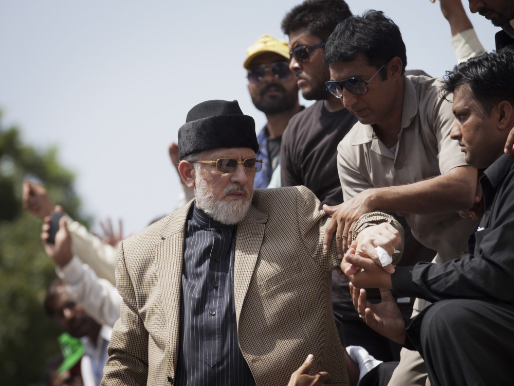 People help Tahir-ul-Qadri down from a stage at a public rally in Islamabad, Pakistan, on Saturday. He and Imran Khan led massive rallies anti-government rallies.