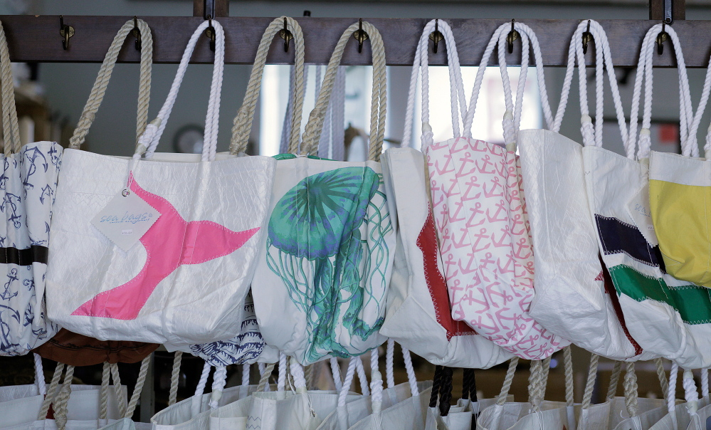 Tote bags made from recycled sails hang in the showroom at Sea Bags in Portland in 2014. It's opening five more stores, three in Maine.