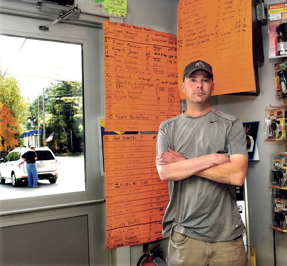 """As a customer pumps gasoline outside Pines Market in Eustis, owner John Morris stands beside the tally boards of the 77 bears that have been tagged this season. The number is twice the amount tagged last year. Morris said if the bear referendum passes it would have an adverse impact on his business. """"There are plenty of bear around this year,"""" Morris said.  David Leaming/Morning Sentinel"""