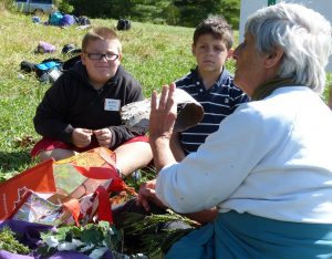 DURING THE FRIENDS OF MERRYMEETING BAY'S BAY DAY for local fourth-graders held in Bowdoinham Tuesday, volunteer Leslie Anderson shows students sample of tree leaves and birch bark, which is waterproof if not torn, once removed in sheets from large trees by are Native Americans to make canoes.