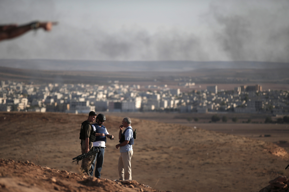 Members of the media talk with a Turkish soldier, left, on a hilltop on the outskirts of Suaruc, at the Turkey-Syria border, overlooking Kobani, Syria, background, during fighting between Syrian Kurds and the militants of Islamic State group, Wedesday.